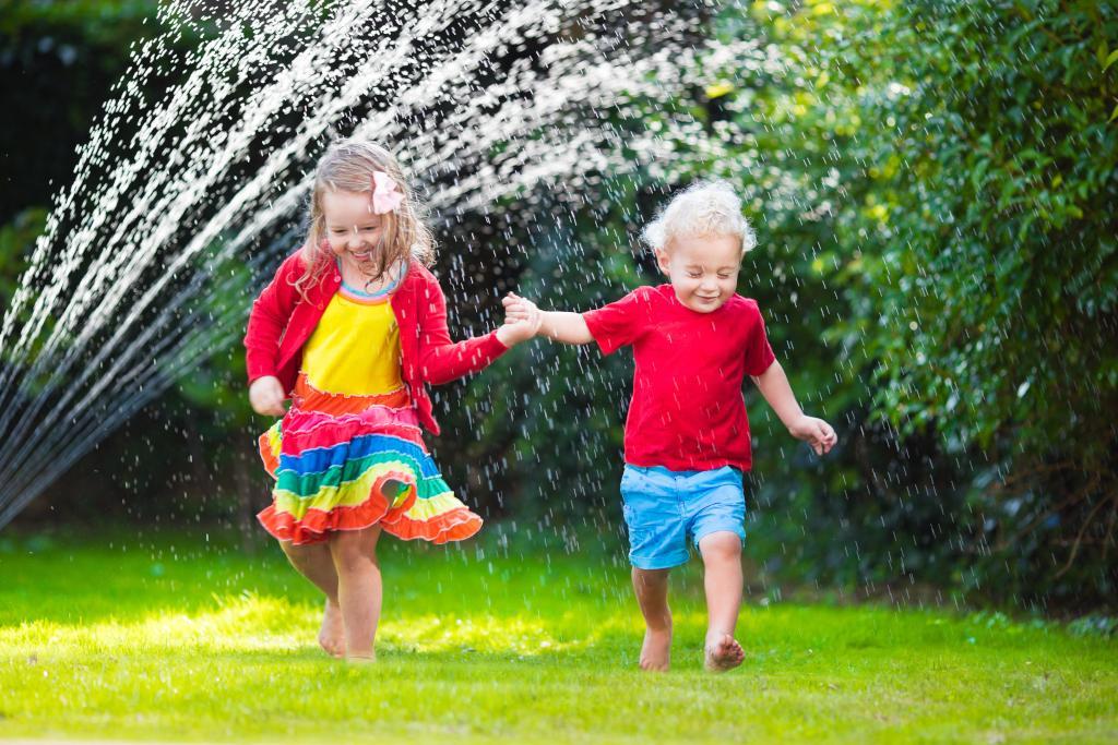 Child,Playing,With,Garden,Sprinkler.,Preschooler,Kid,Run,And,Jump.